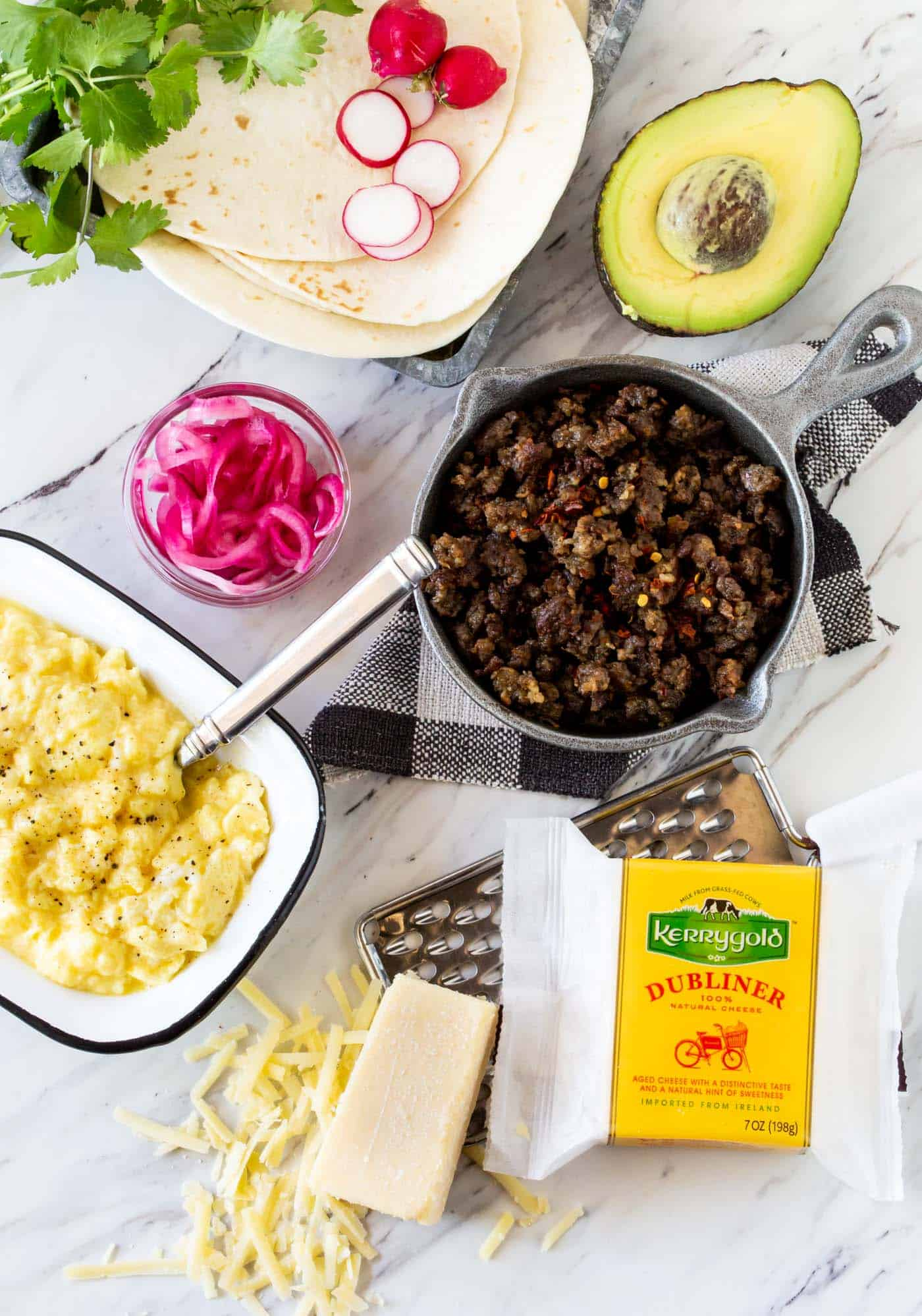 Eggs, sausage, grated Kerrygold Dubliner Cheese, pickled onion, avocado, radishes and cilantro are the toppings for this Make Your Own Breakfast Taco Bar for a Crowd.