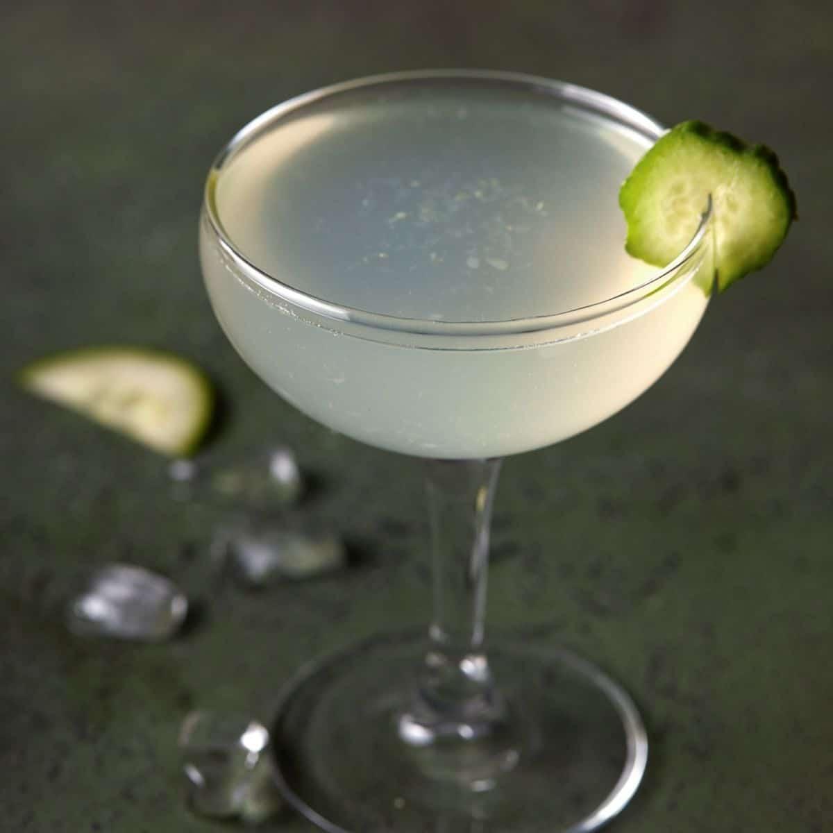Cucumber vodka gimlet in a glass with a cucumber garnish.