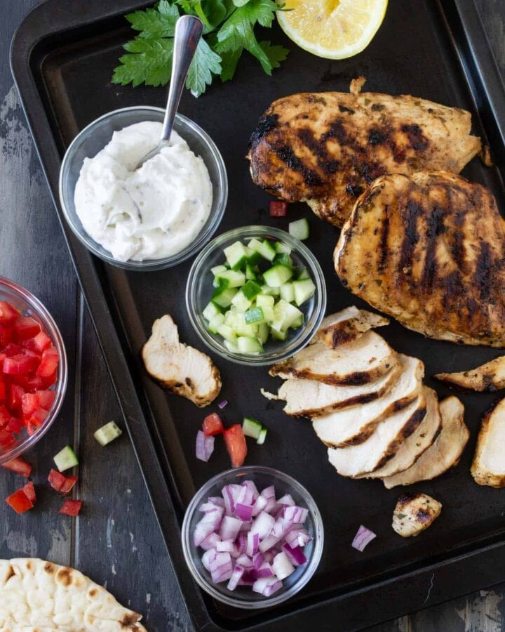 top down image of grilled chicken gyros with sliced onions, chopped cucumber and chopped tomatoes for assembly.