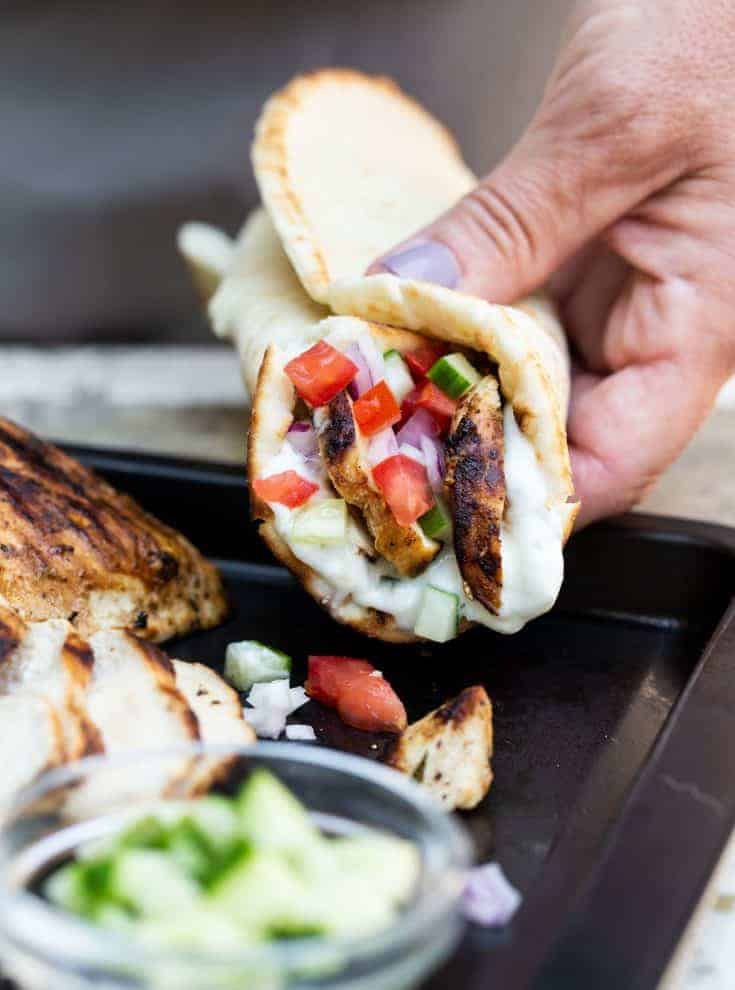 Close up image of hand holding an assembled easy gilled chicken gyro.