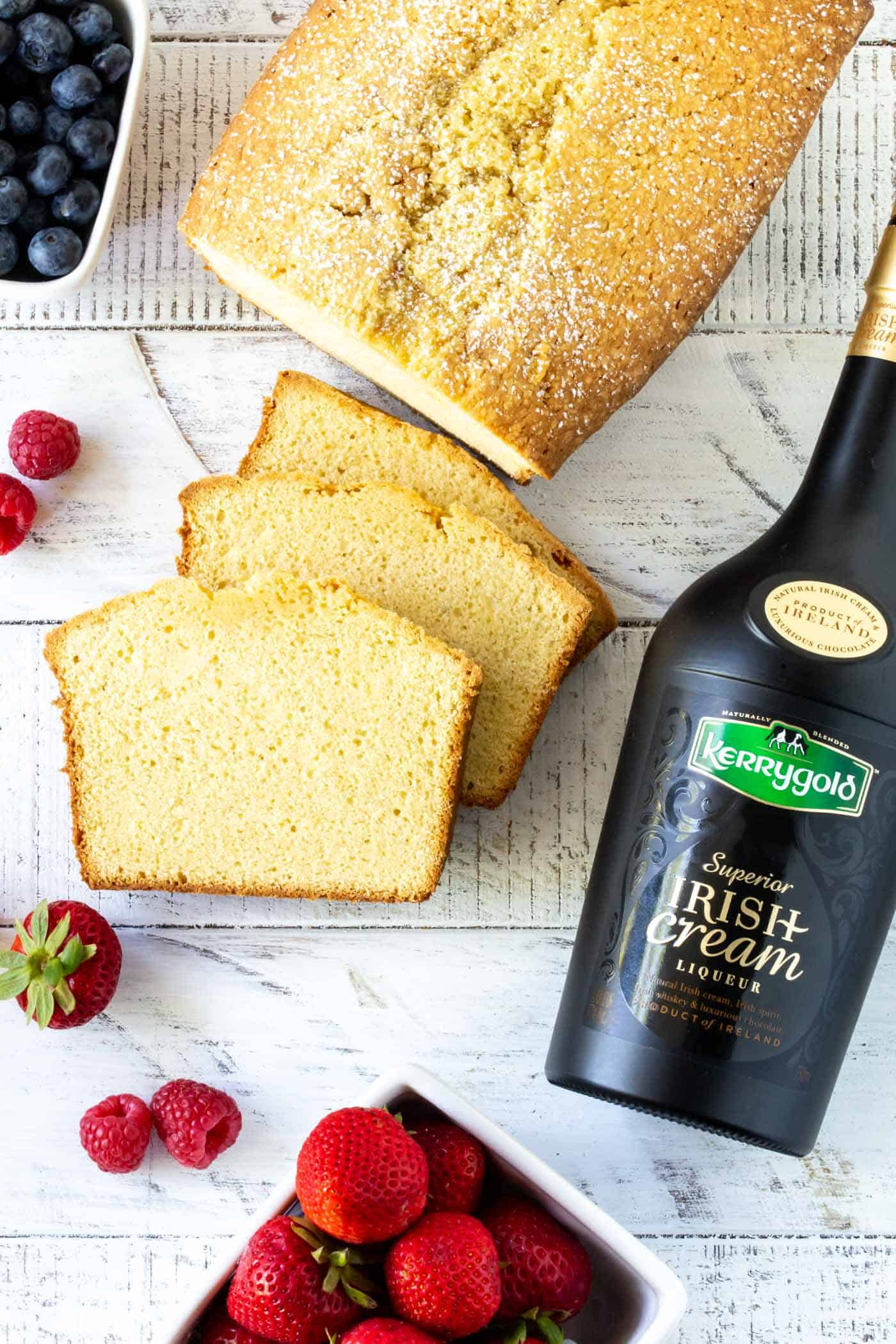 Slices of Irish Cream Pound Cake surrounded by fresh berries and a bottle of Kerrygold Irish Cream Liqueur.