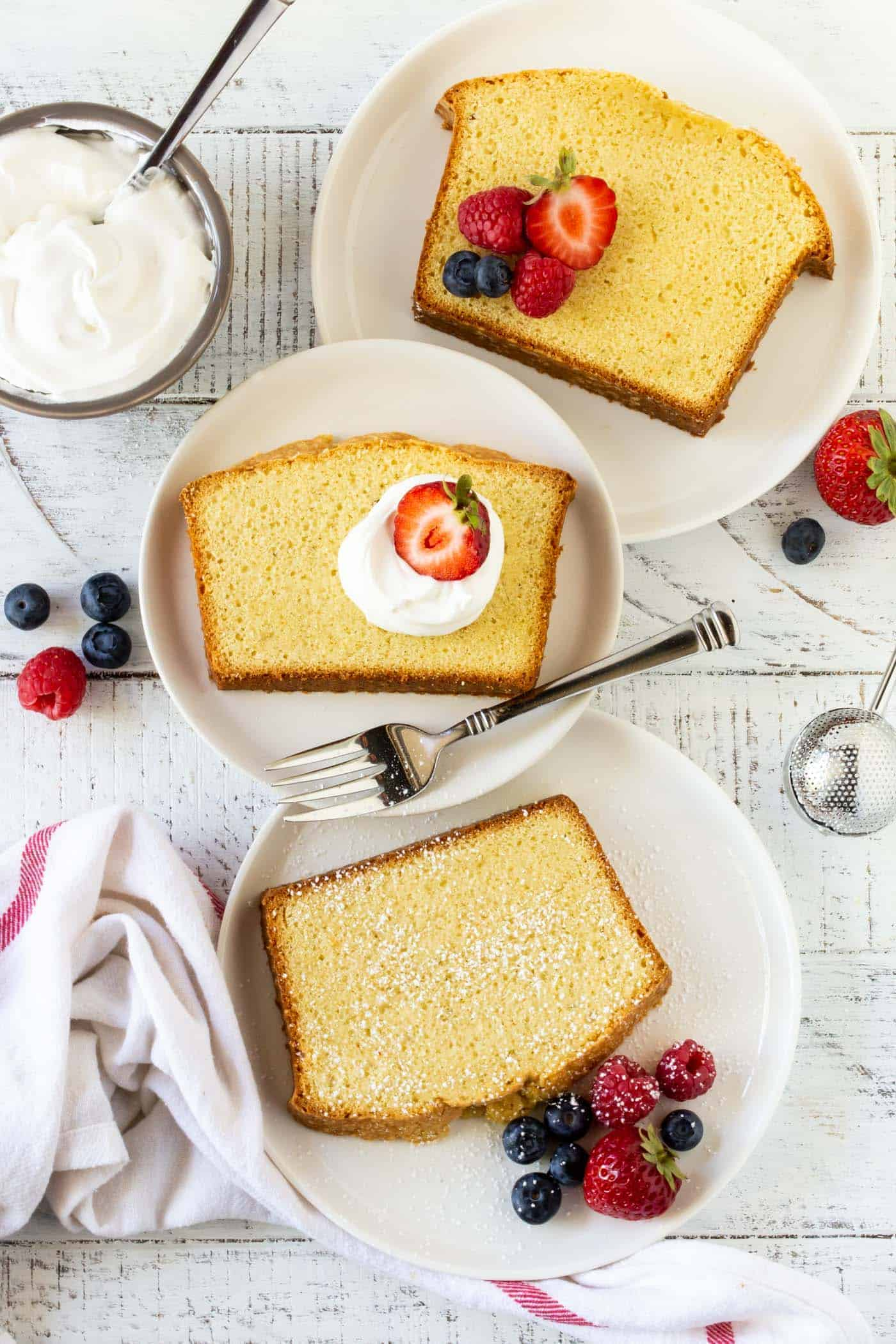 Slices of Irish Cream Pound Cake on round white plates. Garnished with fresh strawberries, raspberries, blueberries, whipped cream and powdered sugar.