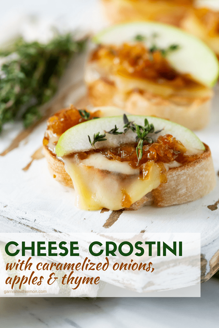 Cheese Crostini with Caramelized Onions, Apples and fresh Thyme on a white wooden board.