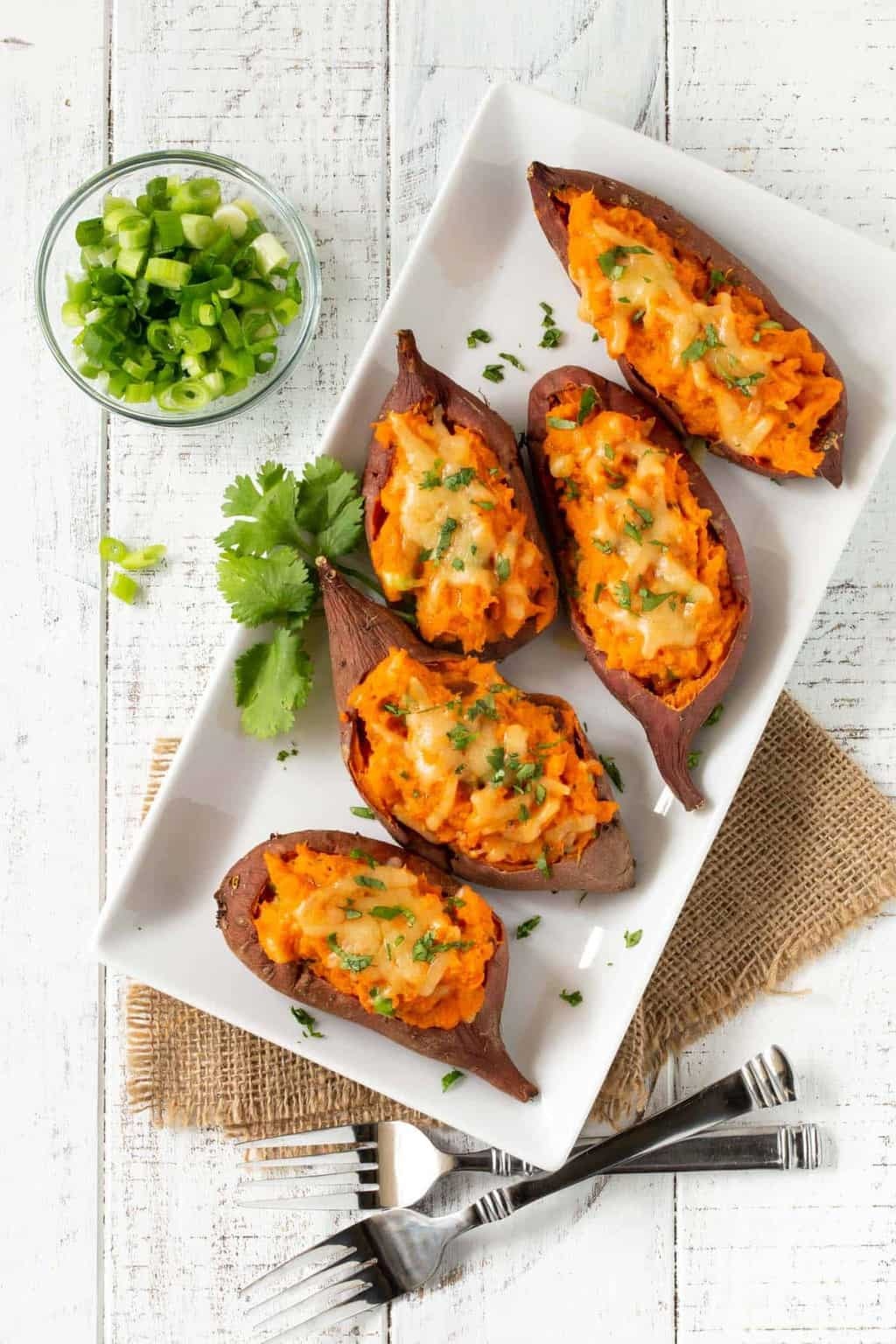 Top down image of Cheesy Chipotle Twice Baked Sweet Potatoes on white tray.