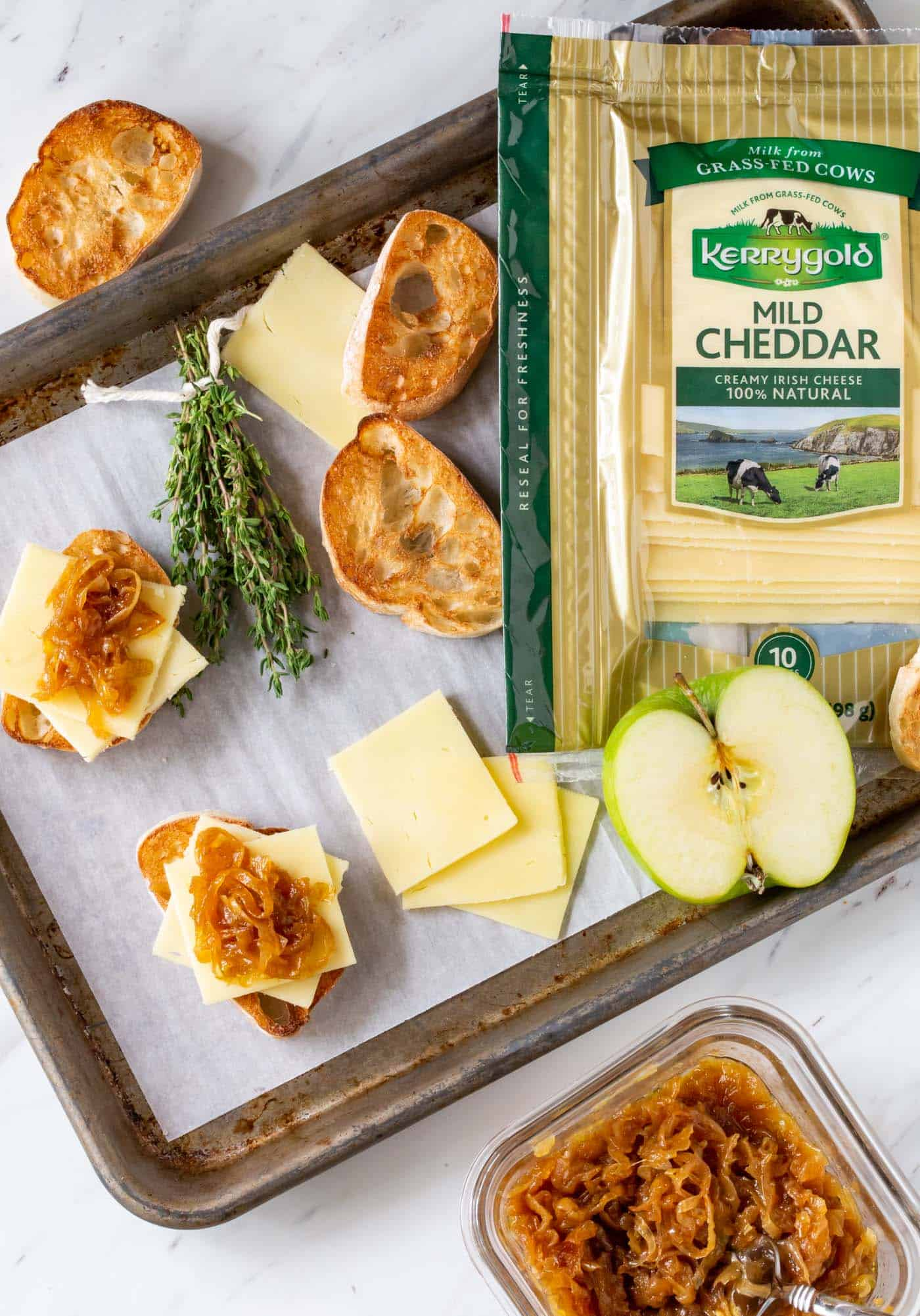 Toasted Cheese Crostini with Caramelized Onions, Apples and Thyme on a Sheet pan with Kerrygold Mild Cheddar Cheese slices.