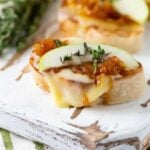 Pieces of Cheese Crostini with Caramelized Onions, Apples and Thyme on a white wooden board.