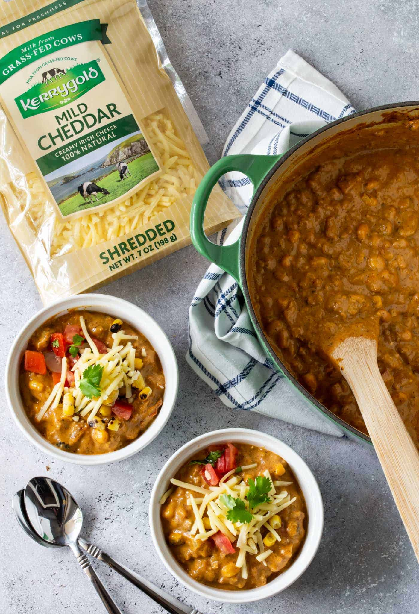 top down image of Creamy Turkey Pumpkin Chili in green dutch oven with white ramekins filled with Creamy turkey pumpkin chili recipe. Garnished with fresh avocado, sour cream and cheese shreds.