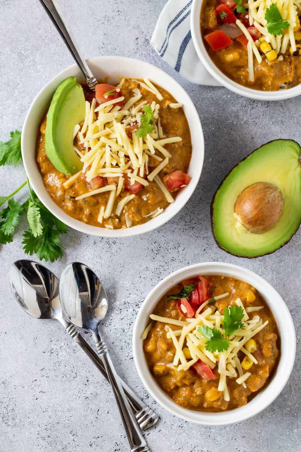 Top down image of Creamy Turkey Pumpkin Chili in white ramekins that are garnishwd with fresh avocado, cheese shreds and cilantro.