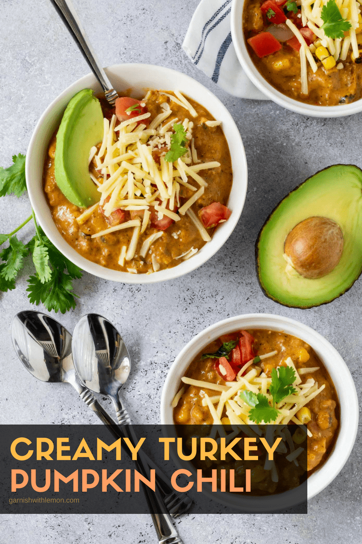 Top down image of white ramekins filled with Creamy Turkey Pumpkin Chili recipe with spoons for eating. Garnished with fresh cilantro, cheese shreds and fresh avocado.