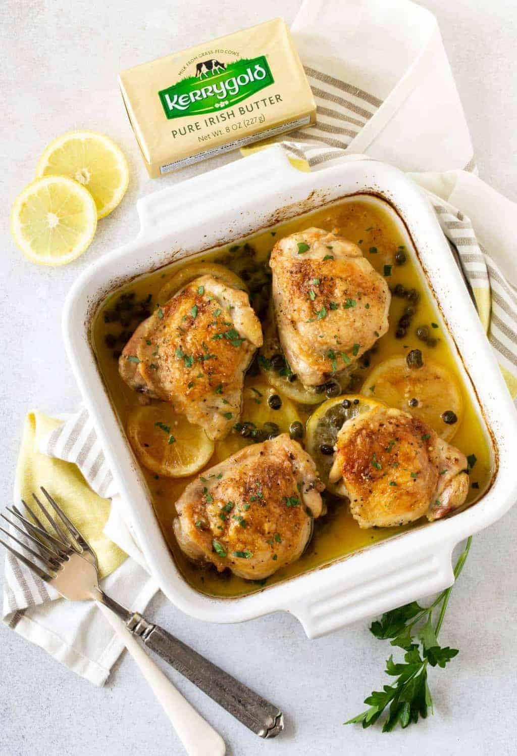 Top down image of Crispy Baked Chicken Thighs in white square baking dish with lemon slices and parsley for garnish.