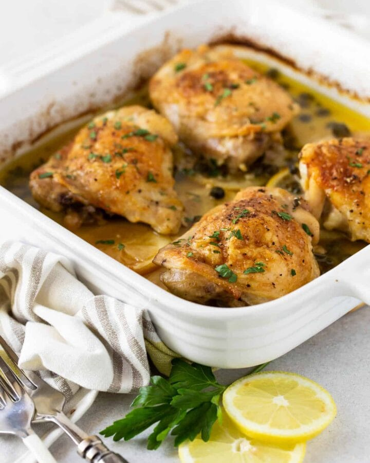 3/4 image of Crispy Baked Chicken Thighs with Capers in a white baking dish with parsley and lemon slices for garnish.