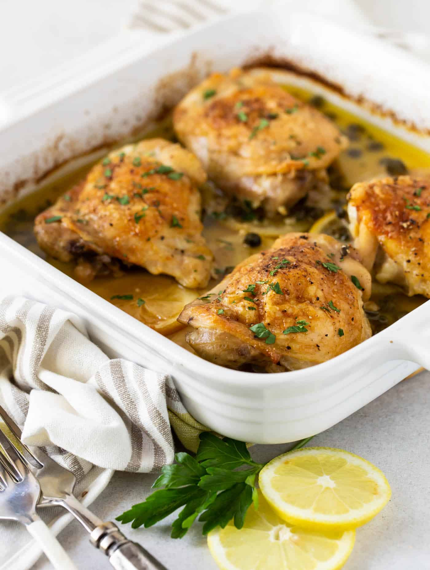 Chicken Thighs with Capers in a white baking dish with parsley and lemon slices for garnish.