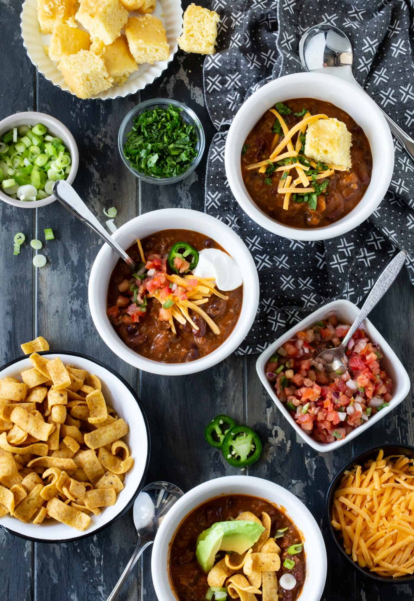Three white bowls filled with chili and surrounded by bowls of chili toppings, including fritos, corn bread, green onions, pico de gallo, cilantro and shredded cheddar cheese.