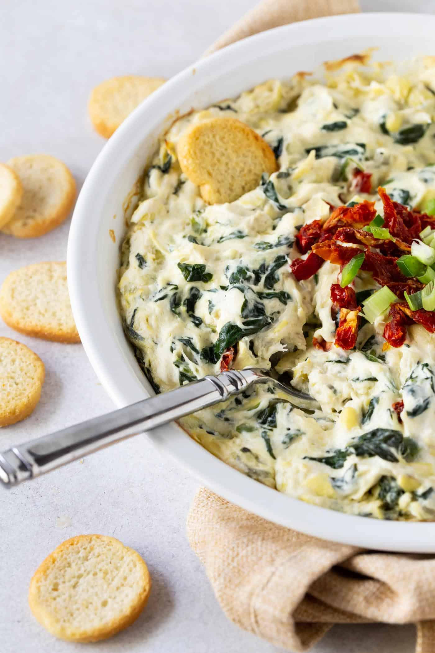 3/4 image of Hot Cheesy Artichoke Crab Dip in white pie plate, garnished with sun-dried tomatoes, shopped green onion and fresh jalapeno on a white background.