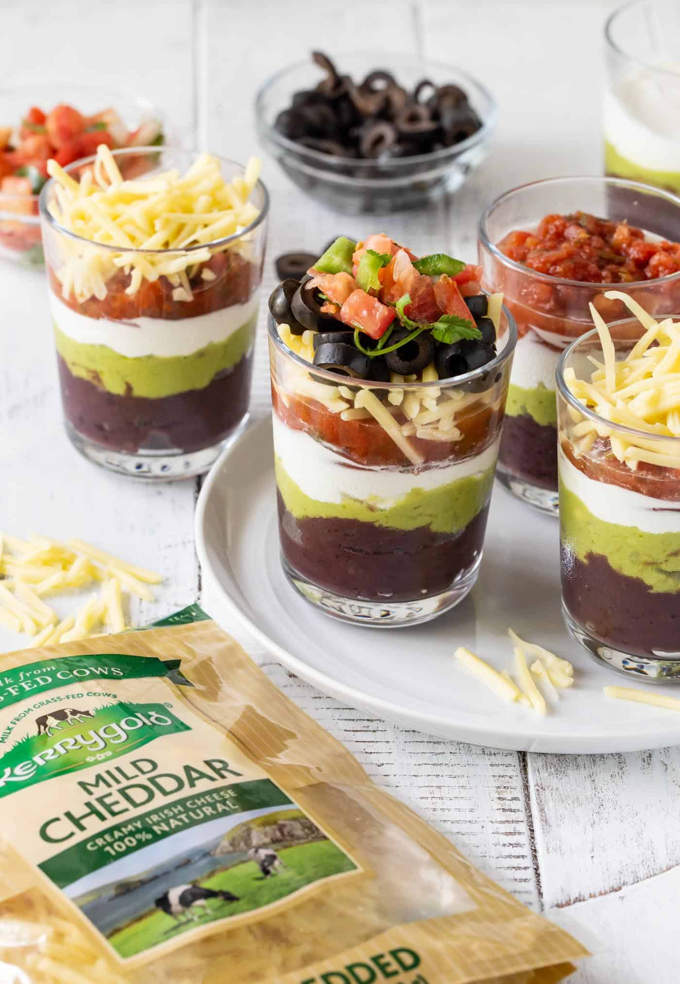 Individual 7 layer Dips in Glass jars with yellow corn tortilla dips.