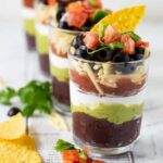 7 layer dips in glass jars with fresh cilantro, black olives and pico de gallo.