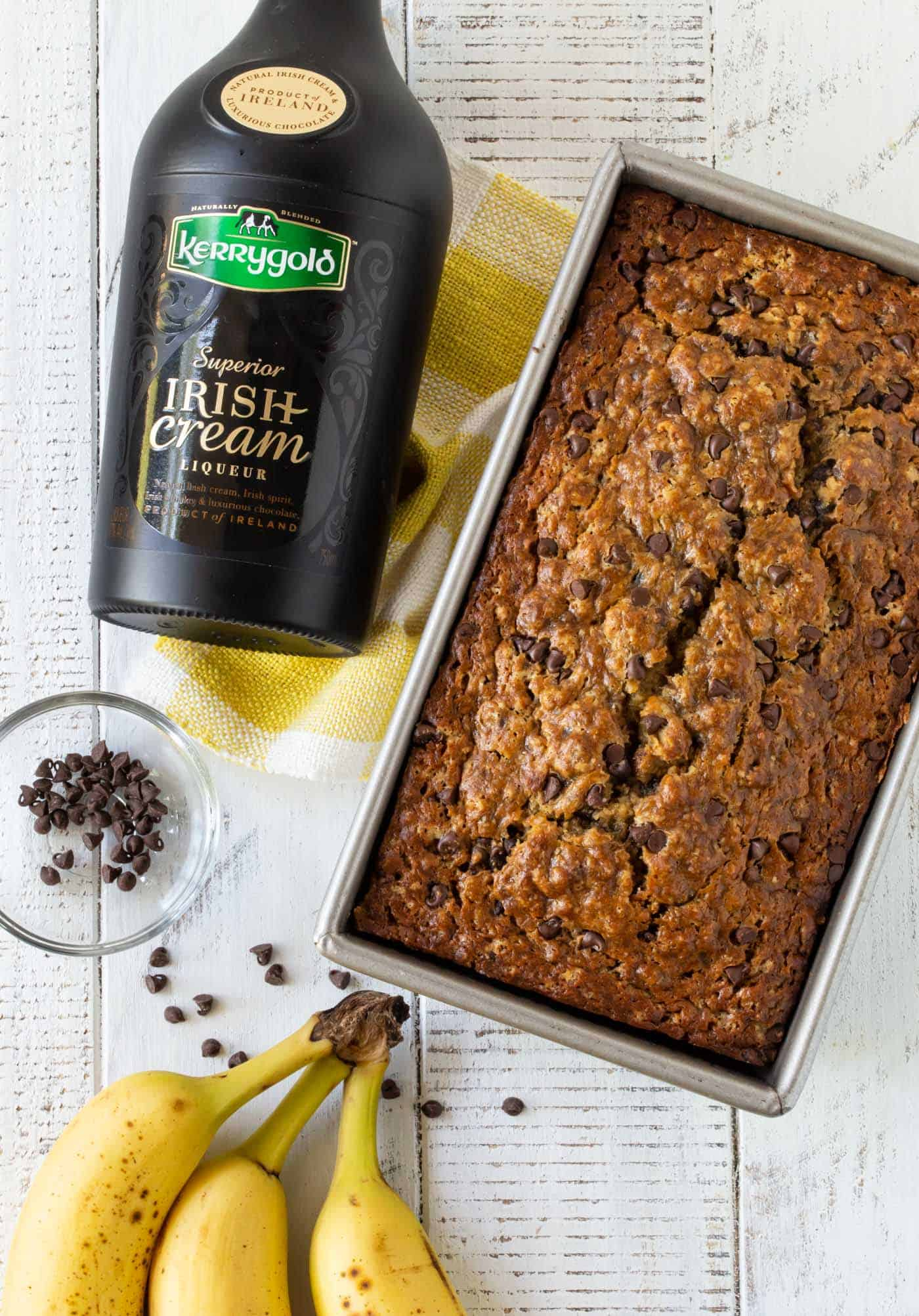 Loaf of Irish Cream Chocolate Chip Banana Bread next to a bottle of Kerrygold Irish Cream Liqueur, a bowl of mini chocolate chips and bananas.