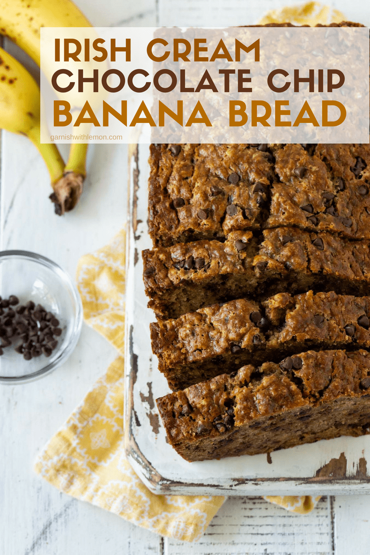 Picture of Irish Cream Chocolate Chip Banana Bread on a white wooden board. Surrounded by mini chocolate chips and bananas.