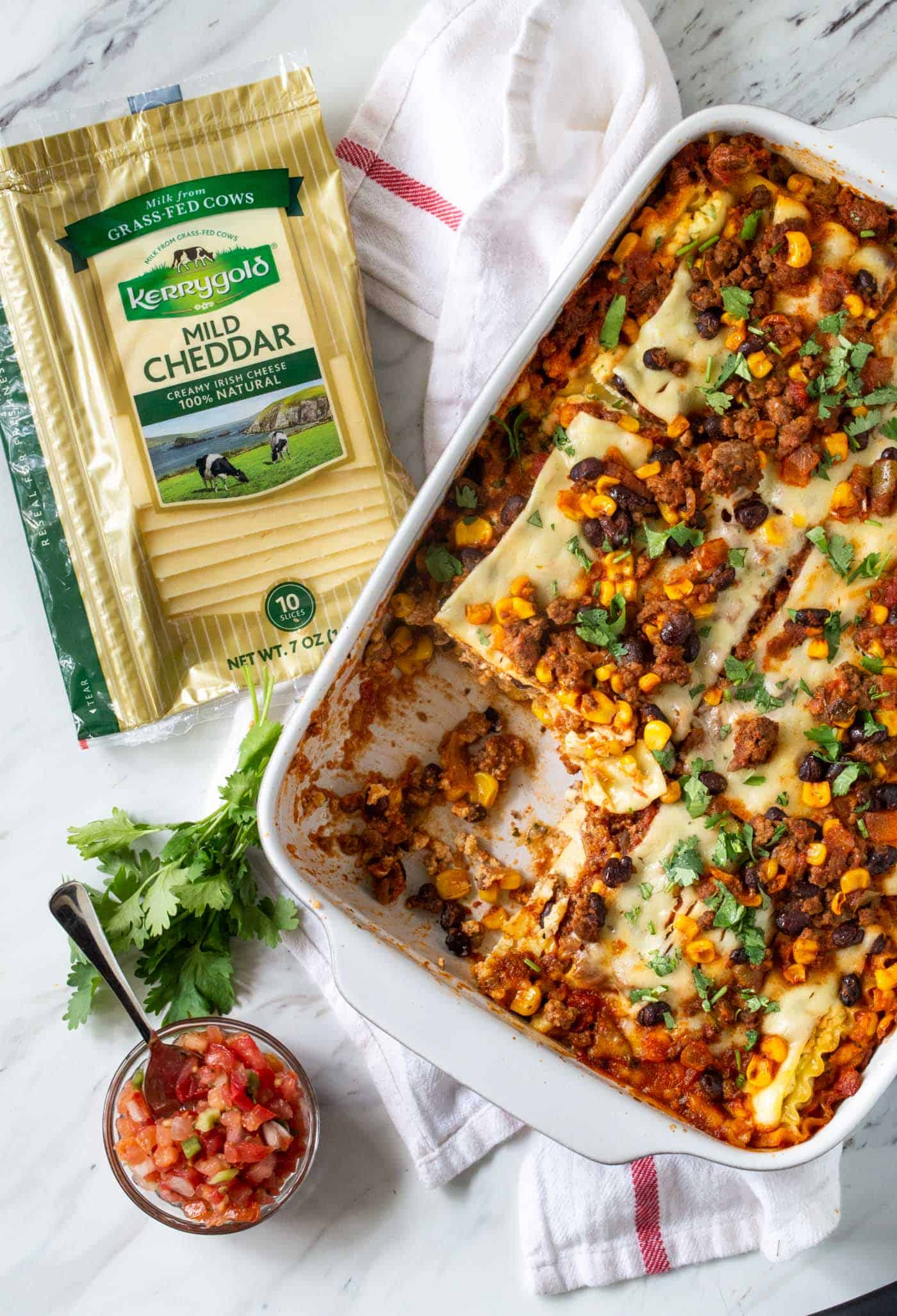 White casserole dish filled with Mexican Lasagna and Kerrygold Mild Cheddar Cheese slices