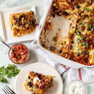 White casserole dish filled with Mexican Lasagna. Two white plates with slices of Mexican Lasagna are nearby.