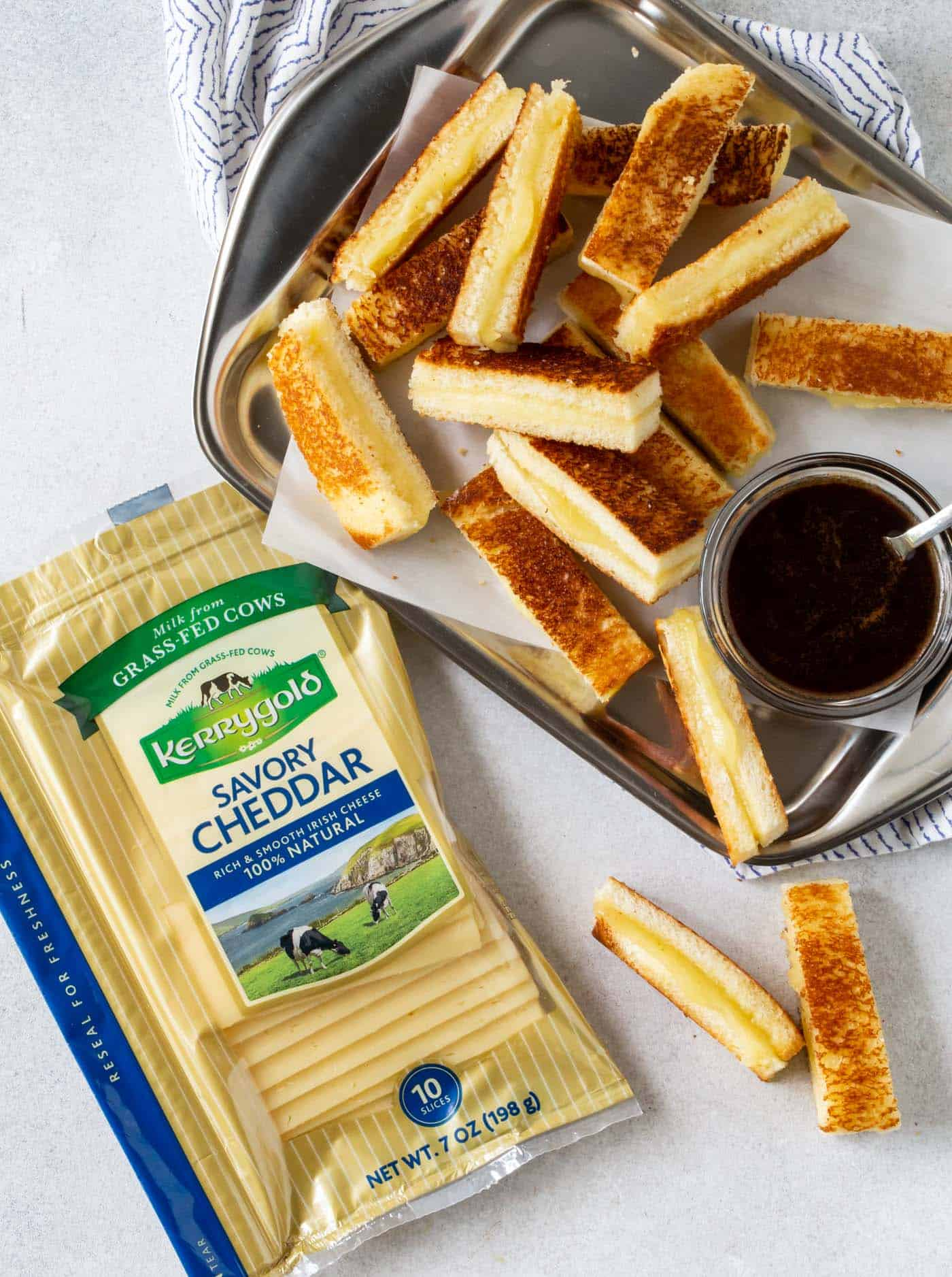 Mini Grilled Cheese Appetizers with Balsamic Dipping Sauce on a silver tray with slices of Kerrygold Savory Cheddar Cheese.