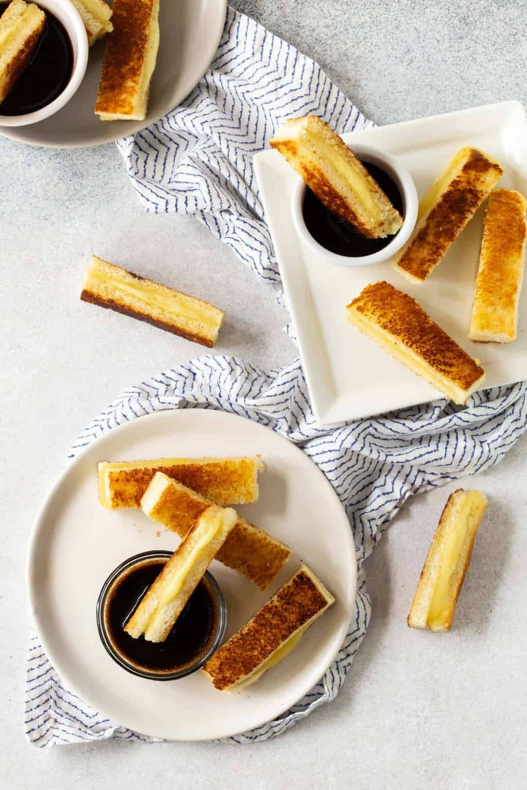 White bowls of Balsamic Dipping Sauce with Mini Grilled Cheese Appetizers.