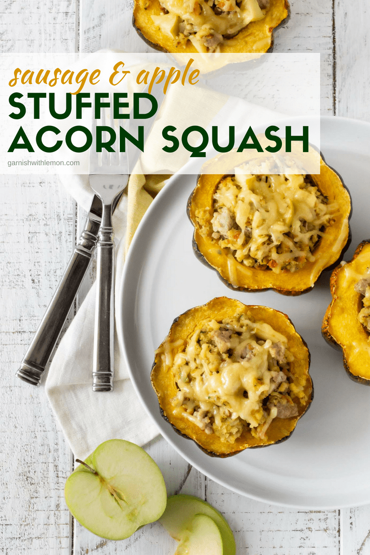 Halves of Apple and Sausage Stuffed Acorn Squash on a white plate with napkin and silverware.