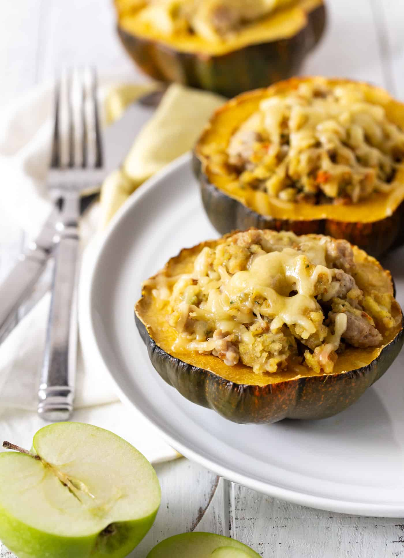2 halves of Apple and Sausage Stuffed Acorn Squash on a white plate with fork and knife.