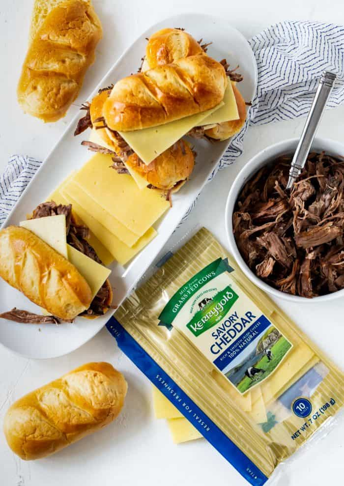 White platter filled with slow cooker french dip sandwiches and surrounded by rolls, Kerrygold Mild Cheddar Cheese slices and a bowl of shredded beef.