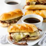 White platter filled with Slow Cooker French Dip Sandwiches and bowls of Au Jus sauce.