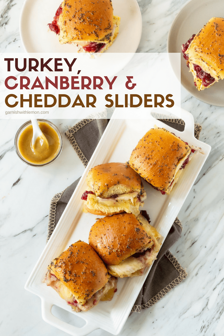 Top down image of Turkey Cranberry and Cheddar Sliders on white plate with mustard sauce on side for garnish.