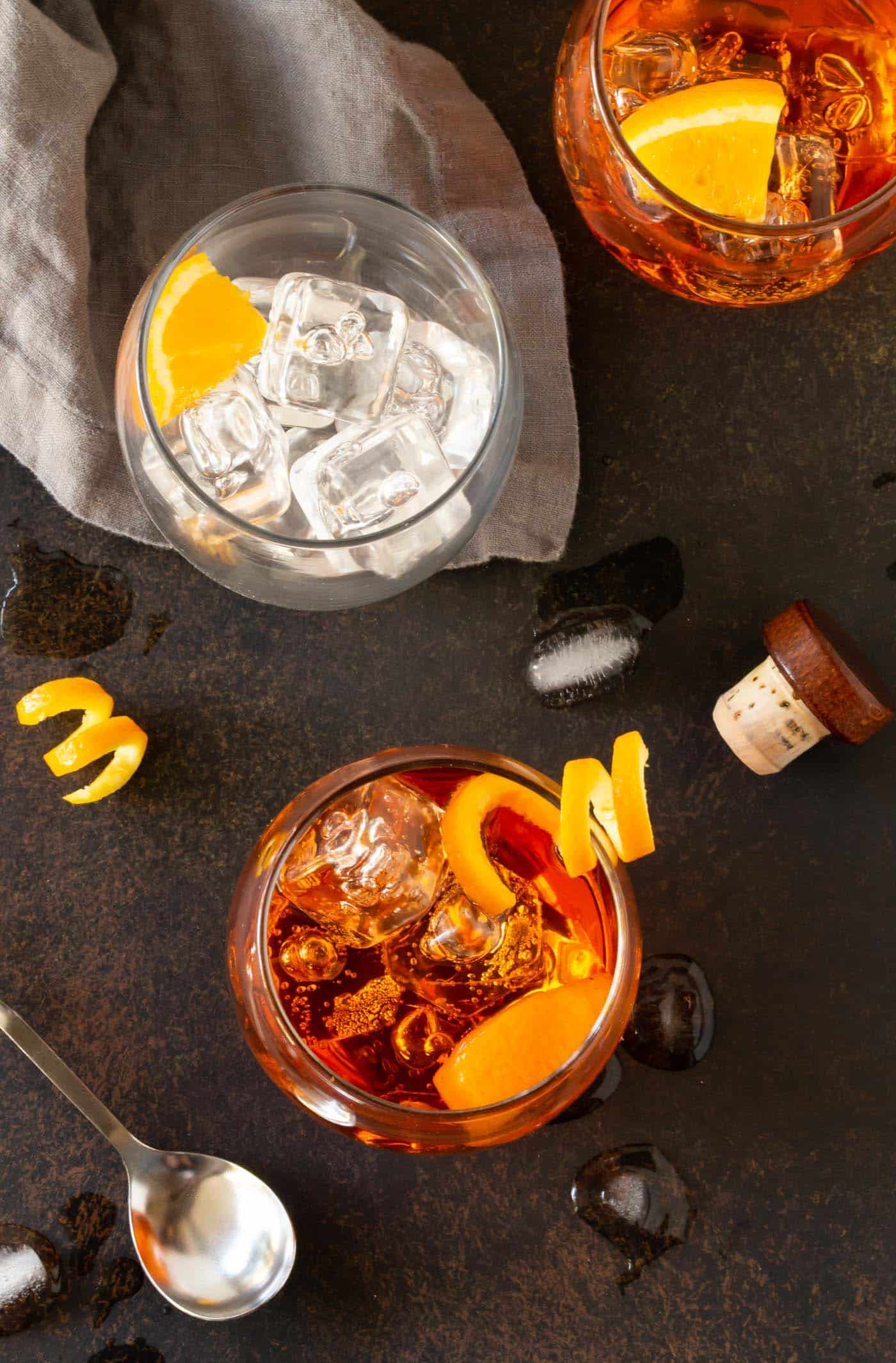 Three low ball glasses filled with ice, orange wedges and Bourbon Aperol Cocktails.