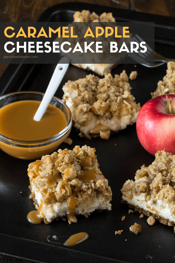 Slices of Caramel Apple Cheesecake Bars on a dark sheet pan. Bowl of caramel sauce for drizzling.