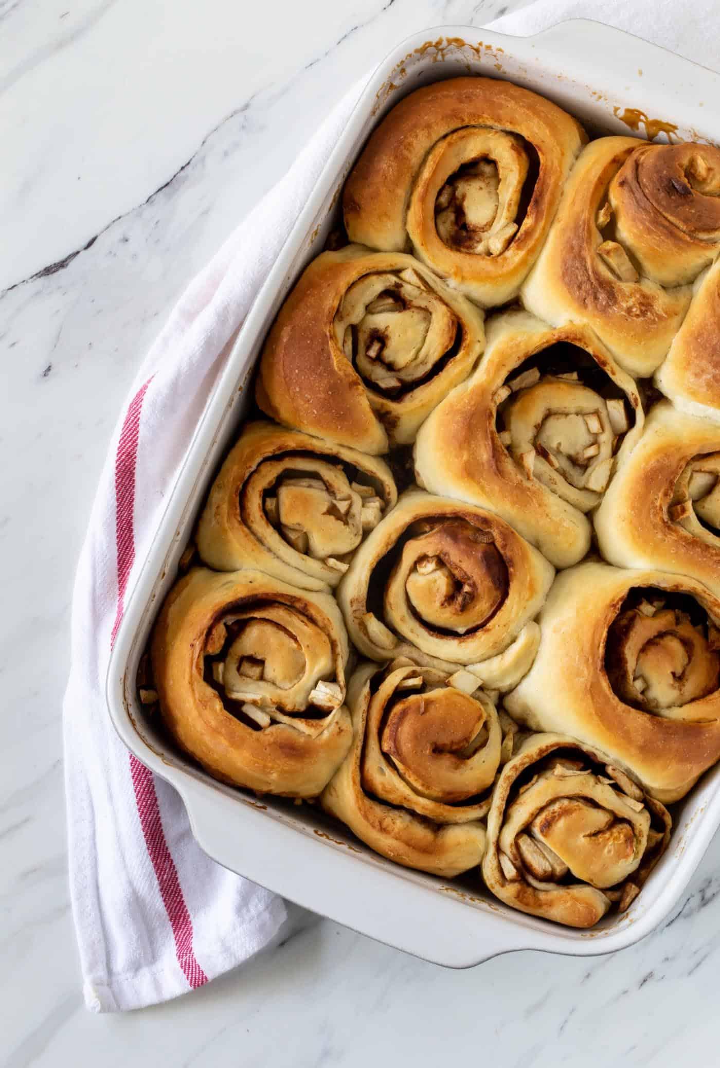 Caramel apple rolls in white baking dish.