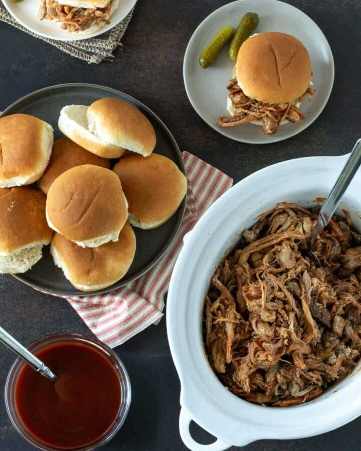 Top down iamge of pulled pork recipe in white slow cooker with buns on side for serving.