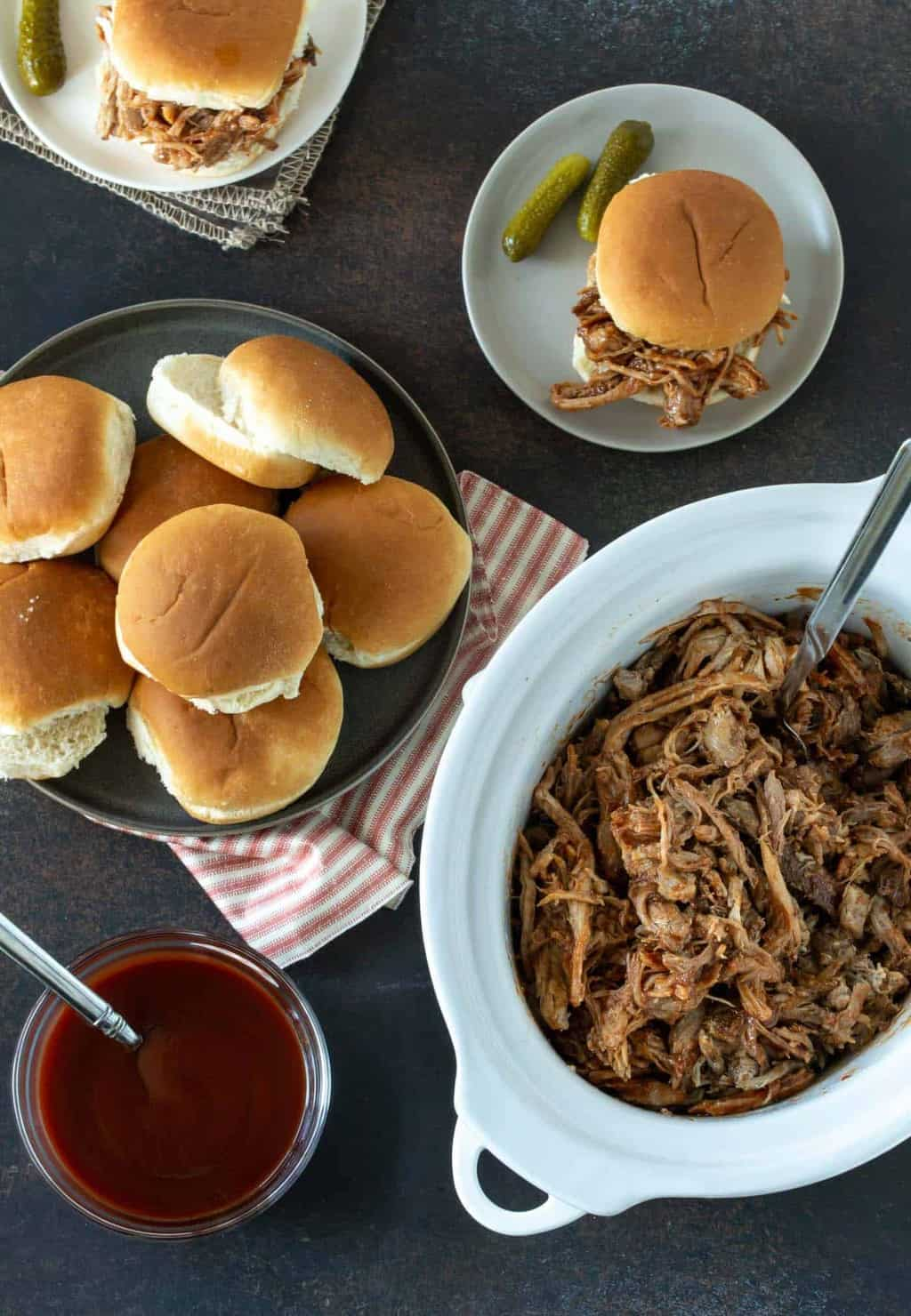 Top down image of pulled pork recipe in white slow cooker with buns on side for serving.