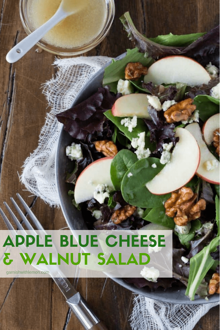 Top down image of apple blue cheese and walnut salad on a dark background with a fork on the side.