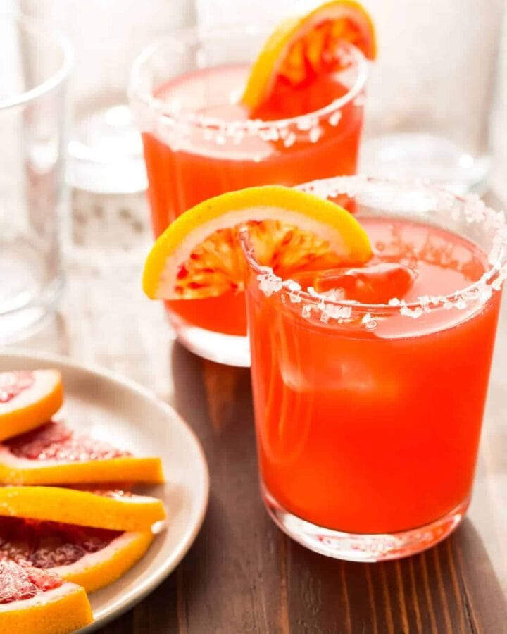 A close up of glasses filled with orange margarita,