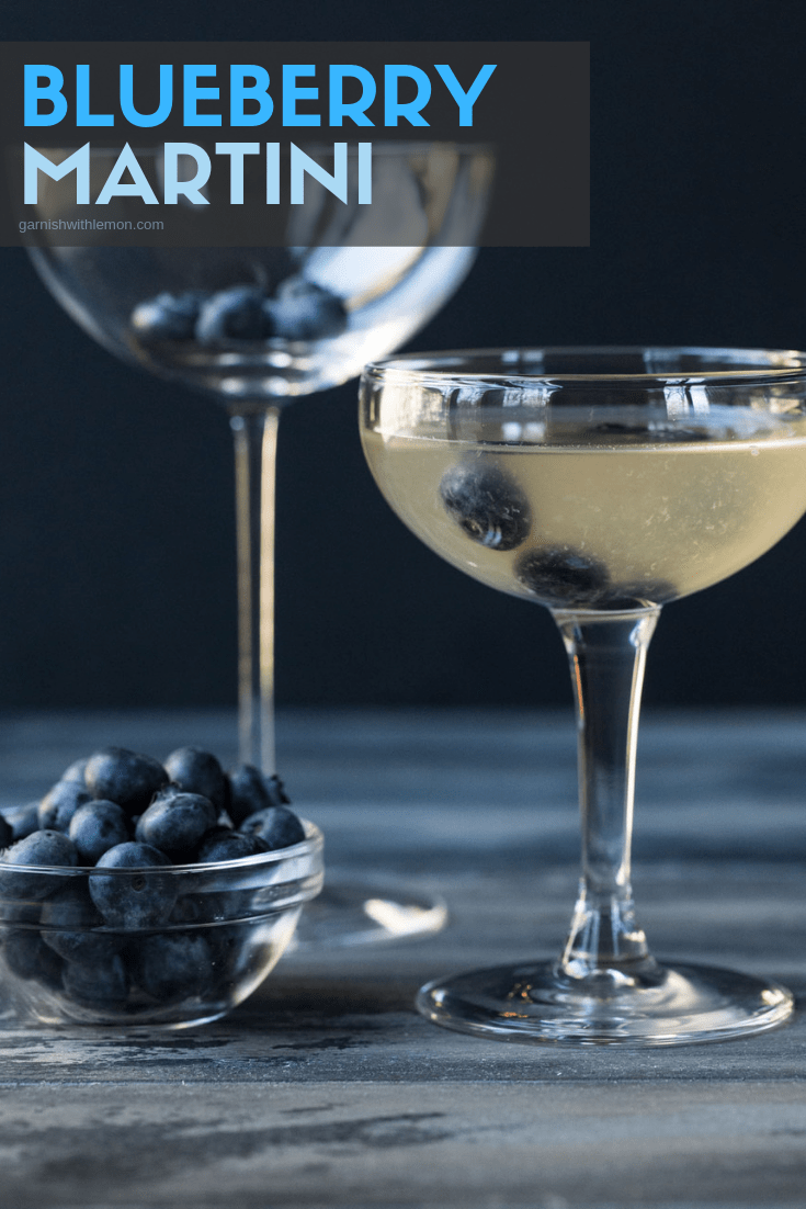 Image of two martini glasses with filled with Blueberry Martini recipe and garnished with fresh blueberries.