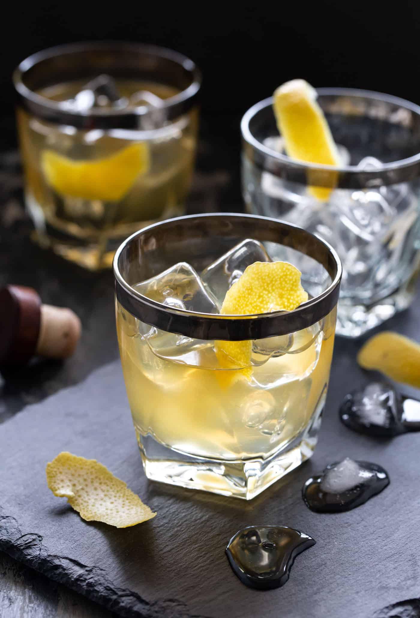 3 low ball glasses filled with Bourbon Elderflower Cocktails on a dark slate board. Garnished with lemon peels.