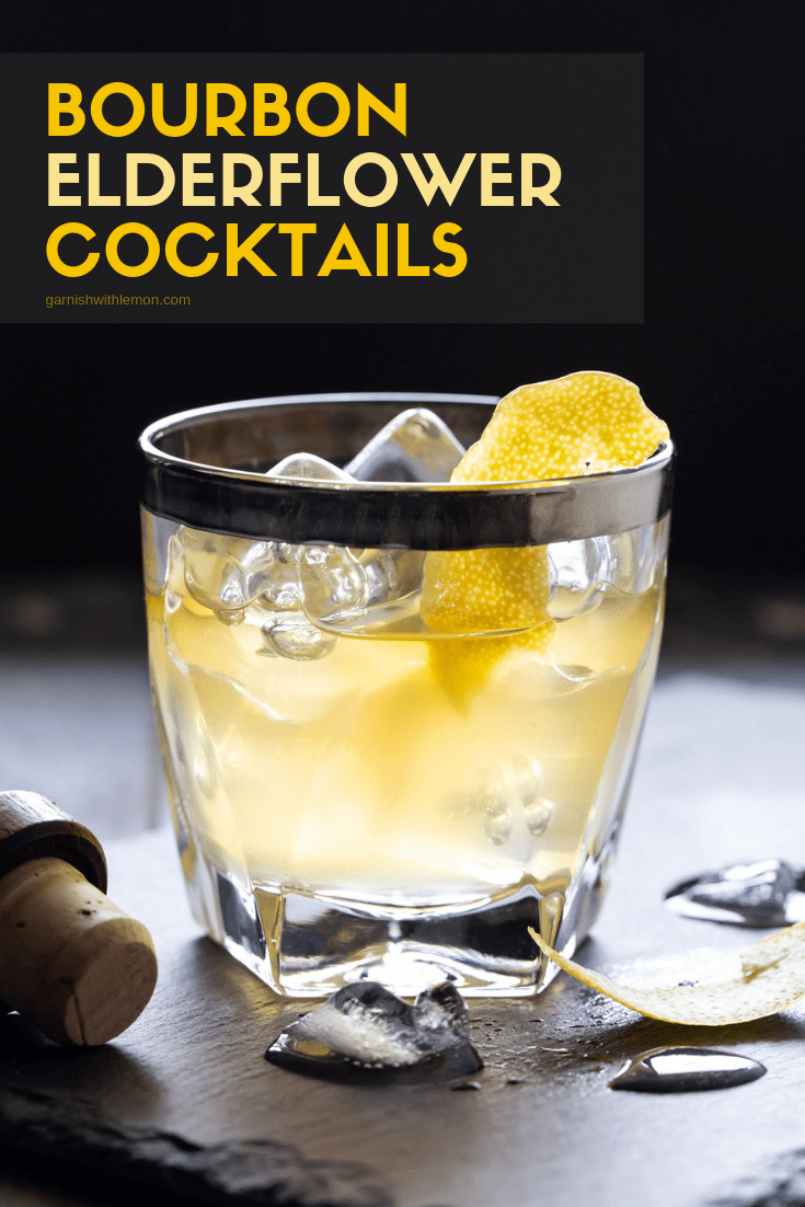 Bourbon Elderflower cocktail in a low ball glass filled with ice, garnished with a lemon peel and on a black slate tray.