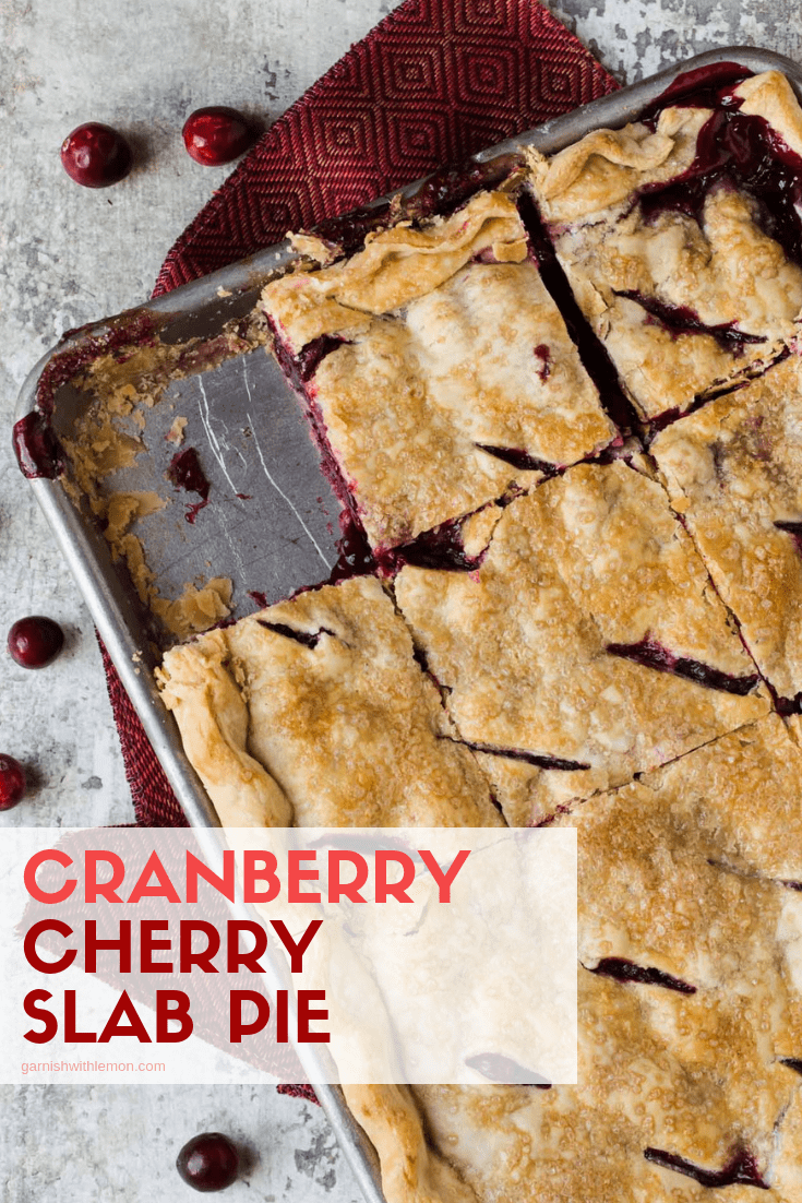 Top down image of Cranberry Cherry Slab Pie with piece cut out and cranberries for garnish.