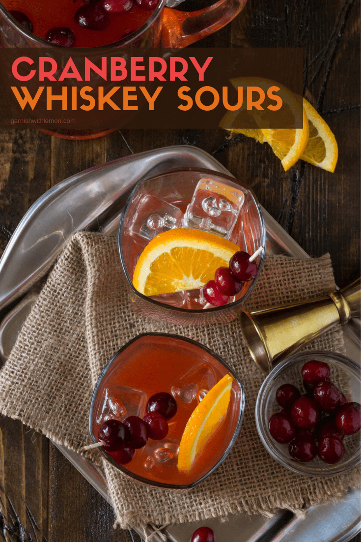 Top down image of Cranberry Whiskey Sours with fresh orange slices and cranberries for garnish on a dark background.