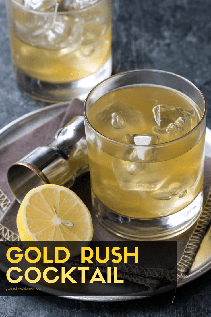 3/4 image of Gold Rush Cocktail in low ball glass with half of lemon and shot glass on side.