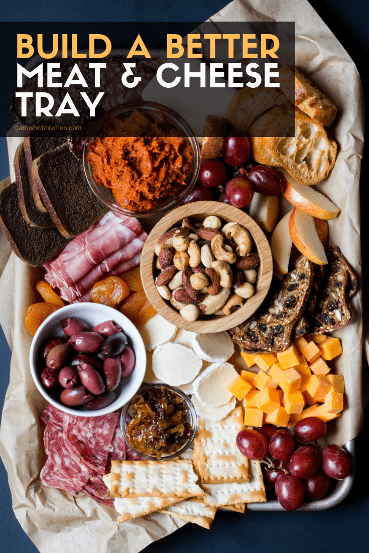 Top down image of meat and cheese platter filled with olives, meats, cheese, grapes and nuts on a dark background.