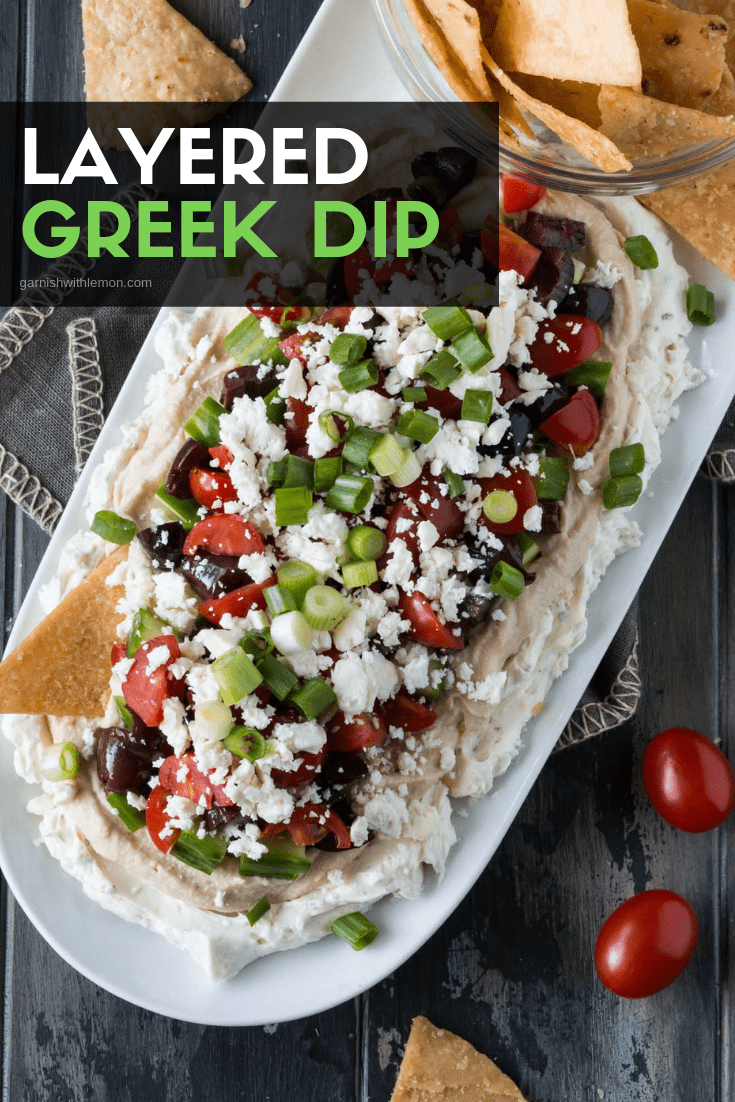 Top down image of Layered Greek Dip on a white platter.