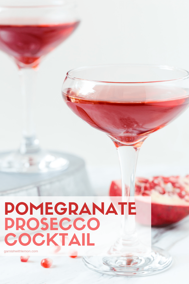 Image of Pomegranate Prosecco Cocktail in coup glass with fresh pomegranate seeds for garnish.
