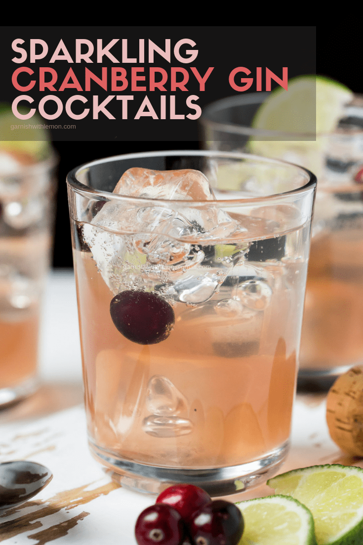 Image of Sparkling Cranberry Gin Cocktail in low ball glass with fresh lime slices and cranberries for garnish.