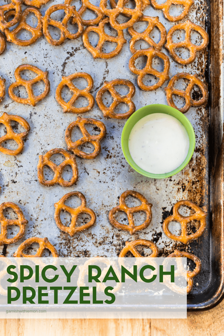 Top down image of spicy ranch pretzels on baking sheet with ranch sauce for dipping.