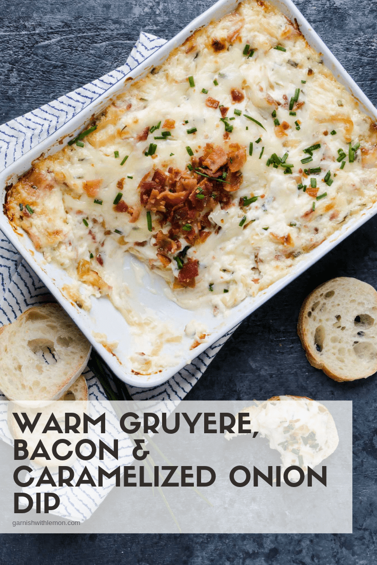 Top down image of Warm Gruyere, bacon and Caramelized Onion Dip on a slate background with crostini for eating.